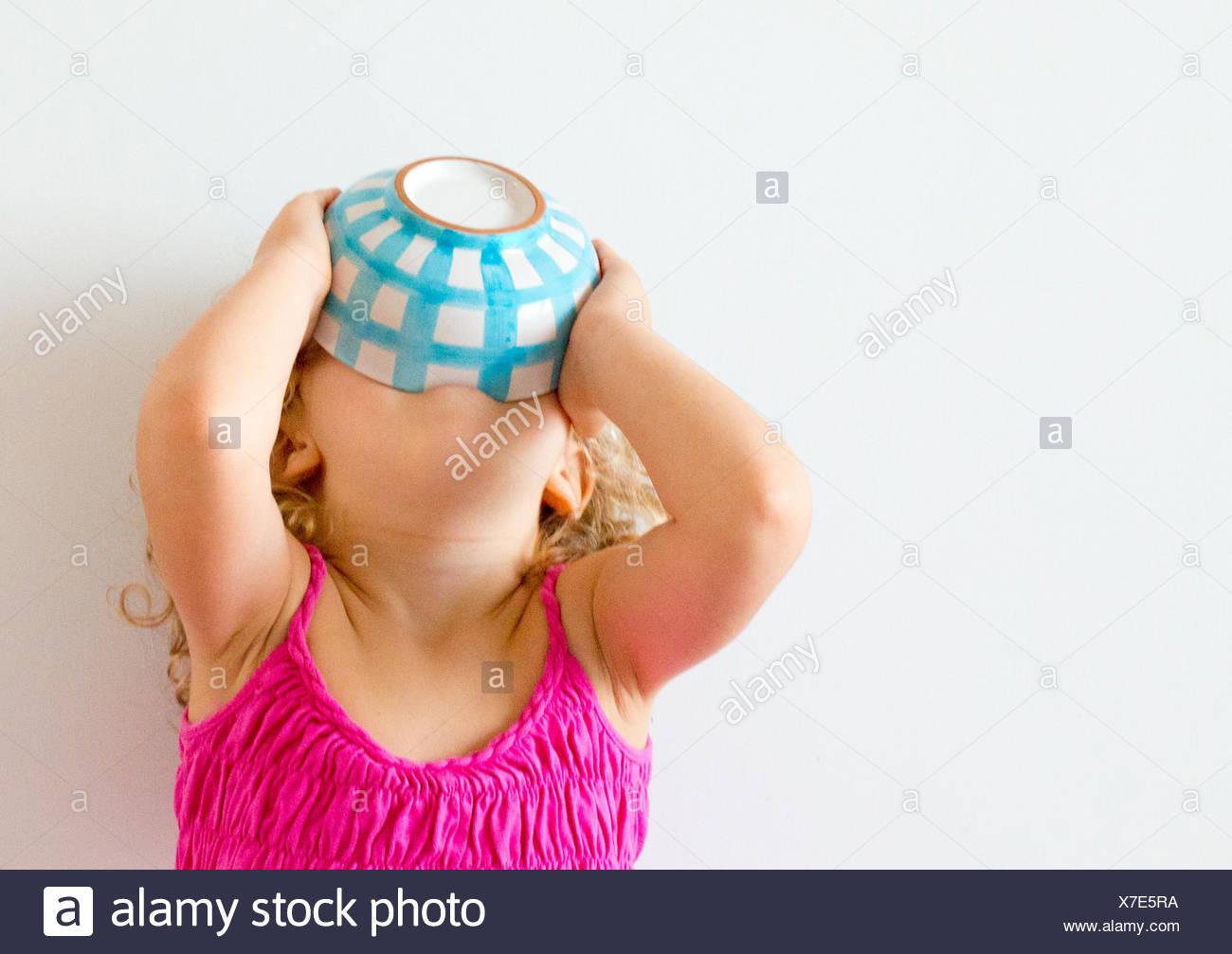 Fille avec tête en arrière maintenant bol de céréales à sa bouche Photo Stock