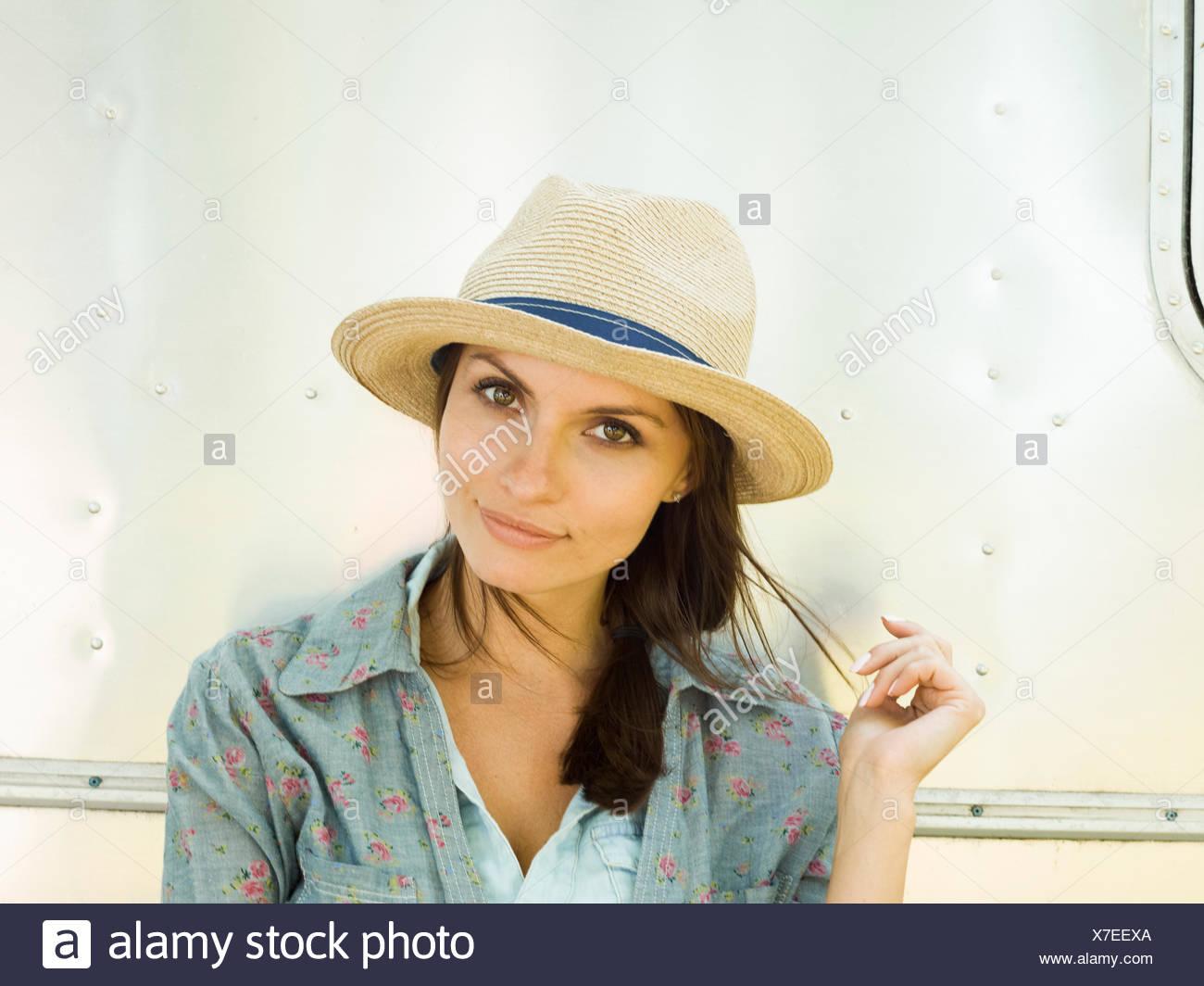 Une jeune femme d'un chapeau de paille, sa tête inclinée à curieux. Photo Stock