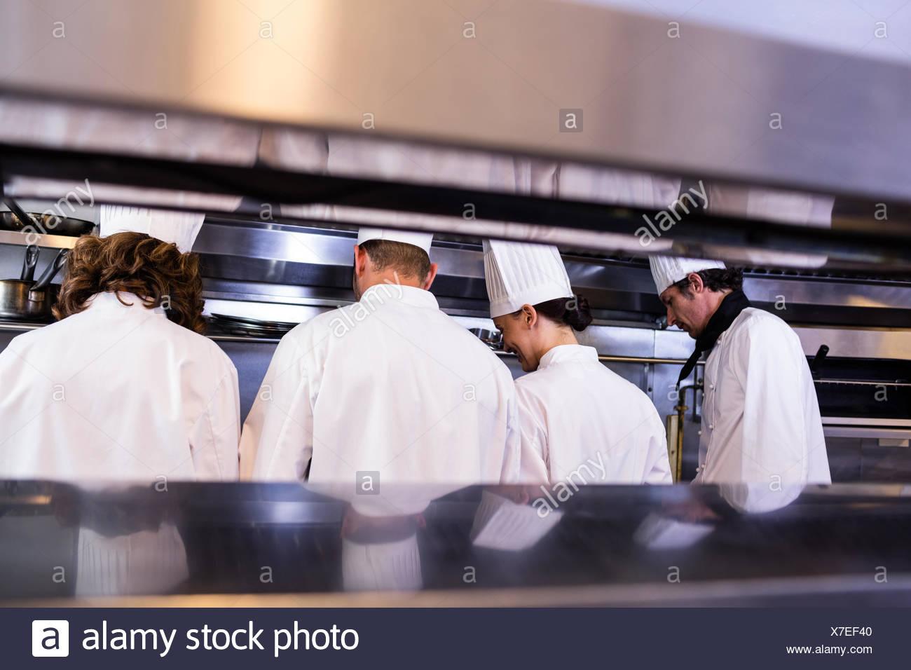 Groupe des chefs en uniforme blanc occupé pour la préparation des aliments Photo Stock