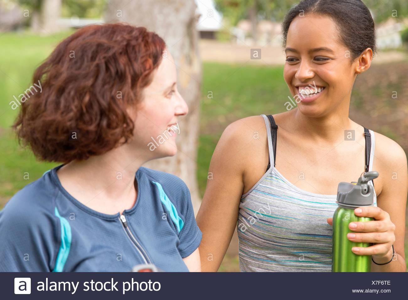 La tête et les épaules des jeunes femmes portant de l'eau bouteilles face à face smiling Photo Stock