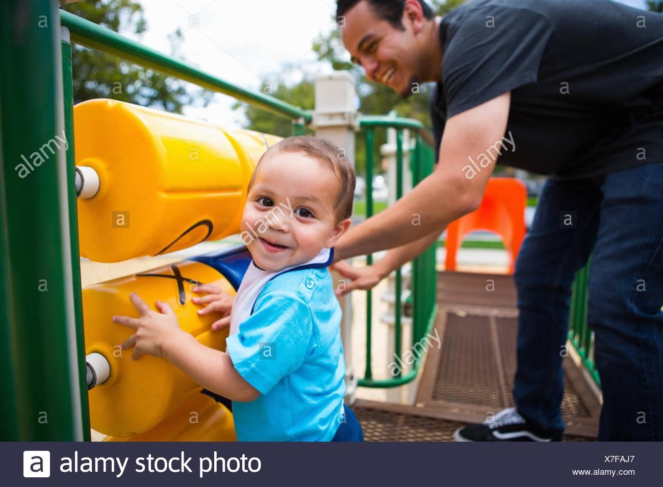 Jeune homme jouant avec tout-petit frère à l'équipement de jeu Photo Stock