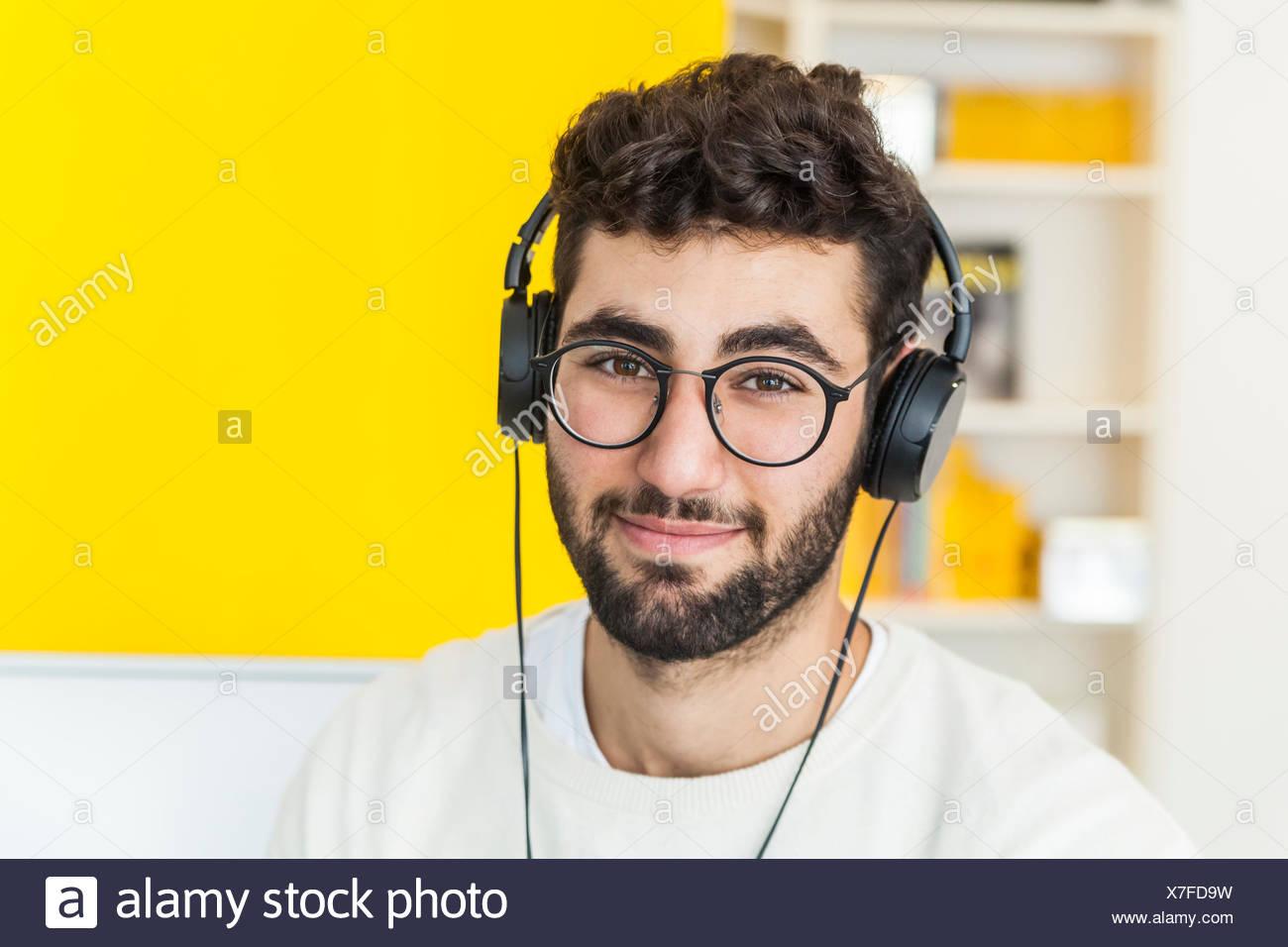 Portrait of smiling man avec des lunettes et des écouteurs Photo Stock