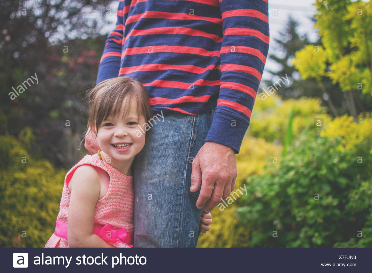 Close-up of a Smiling girl hugging father's leg Photo Stock