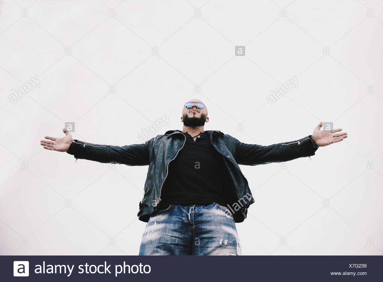 Low angle view of a cool man with arms outstretched Photo Stock