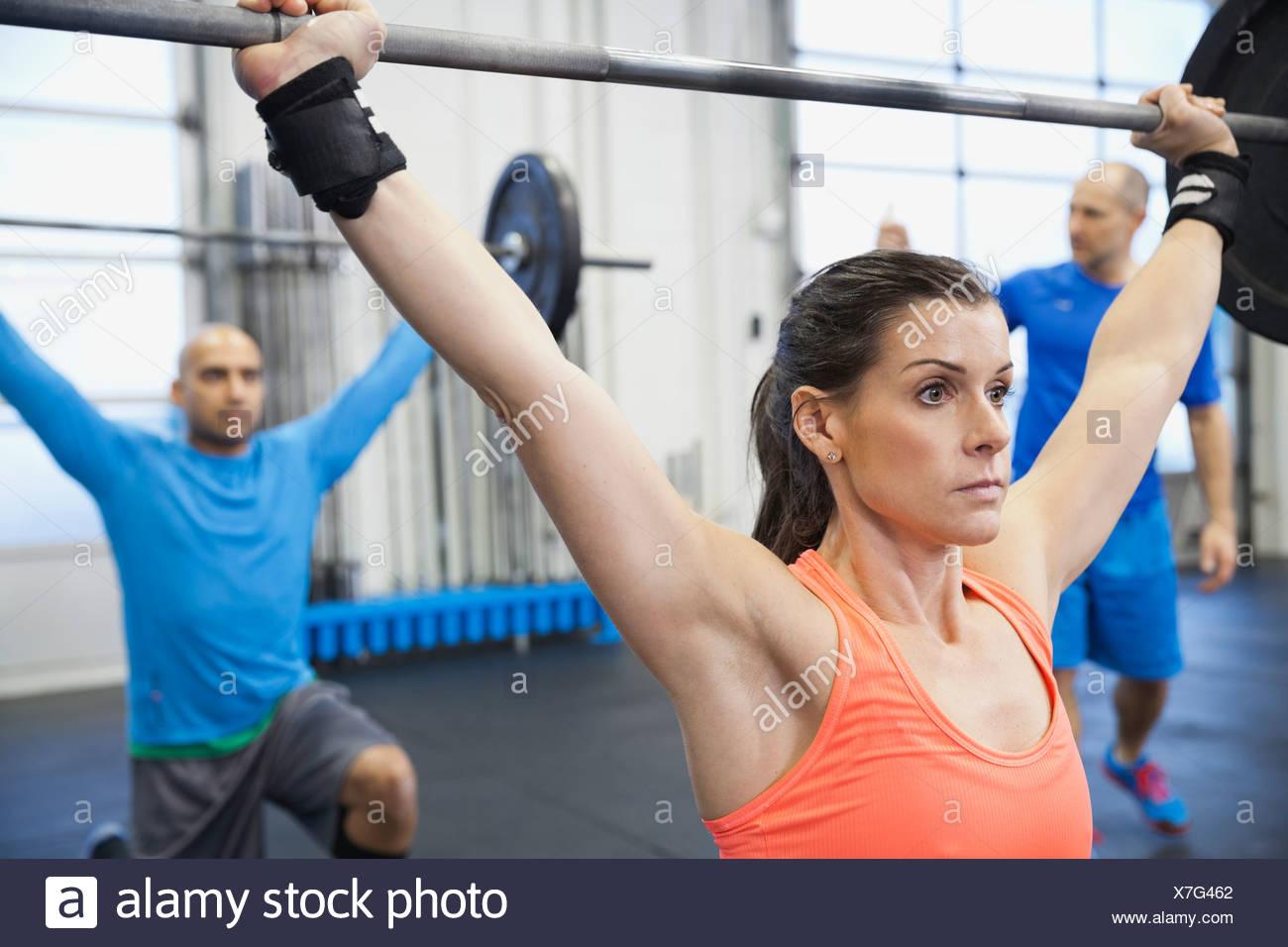 Femme déterminée faisant traverser monter en salle de sport Photo Stock