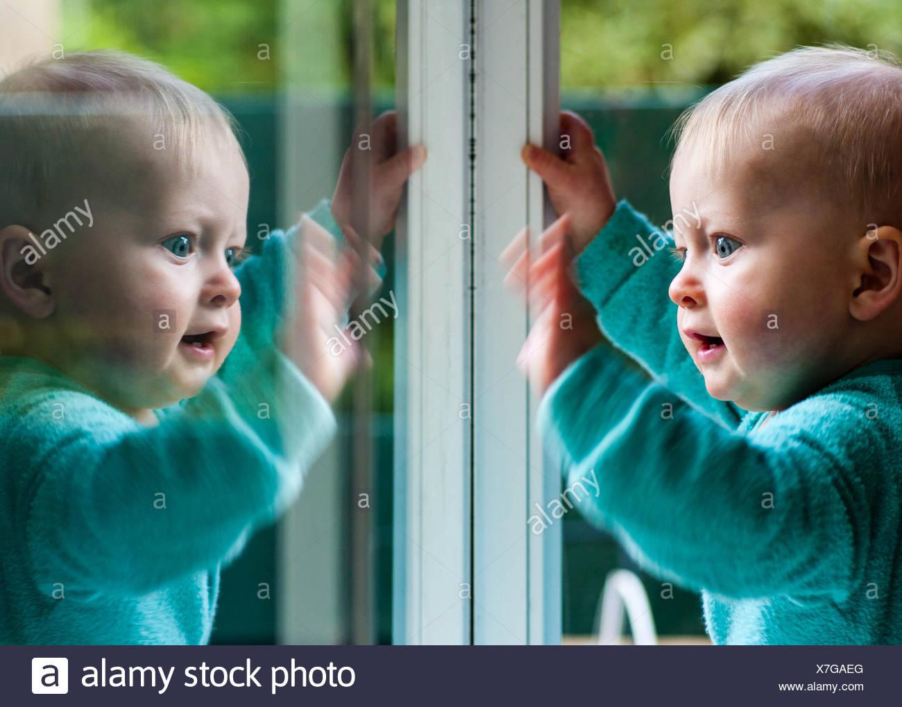 Bébé Garçon jouant avec son reflet dans la fenêtre Photo Stock