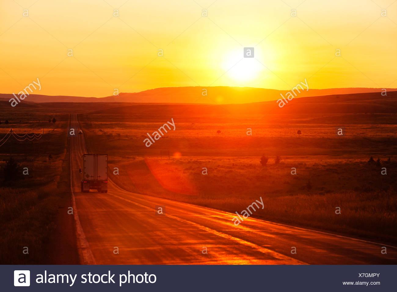 Un camion de livraison sur une longue ligne droite de la route à l'aube, dans le Montana. Photo Stock