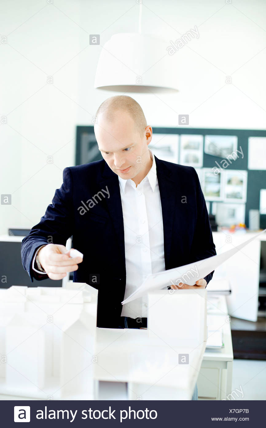 L'homme examinant maisons modèles Photo Stock
