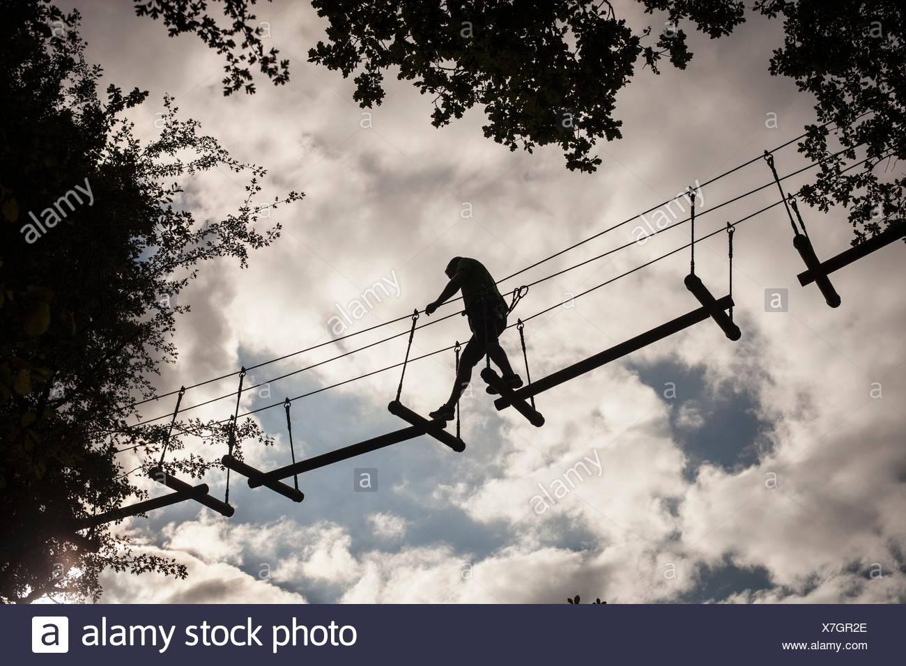 Homme mûr, corde haute marche, low angle view Photo Stock