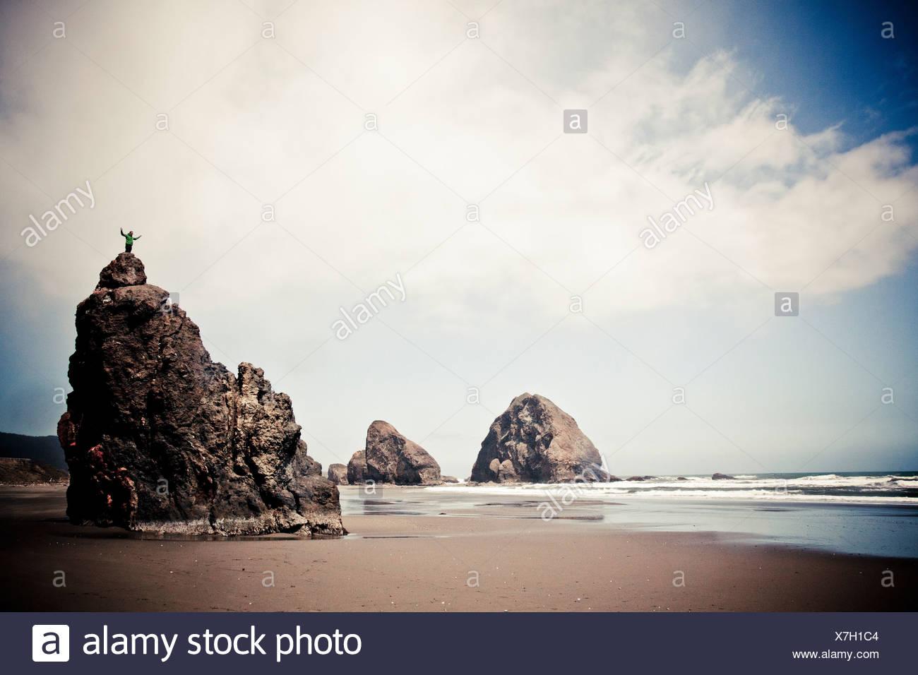 Un grimpeur se dresse sur un monolithe à Pistol River State Park, sur la côte de l'Oregon, USA. Photo Stock