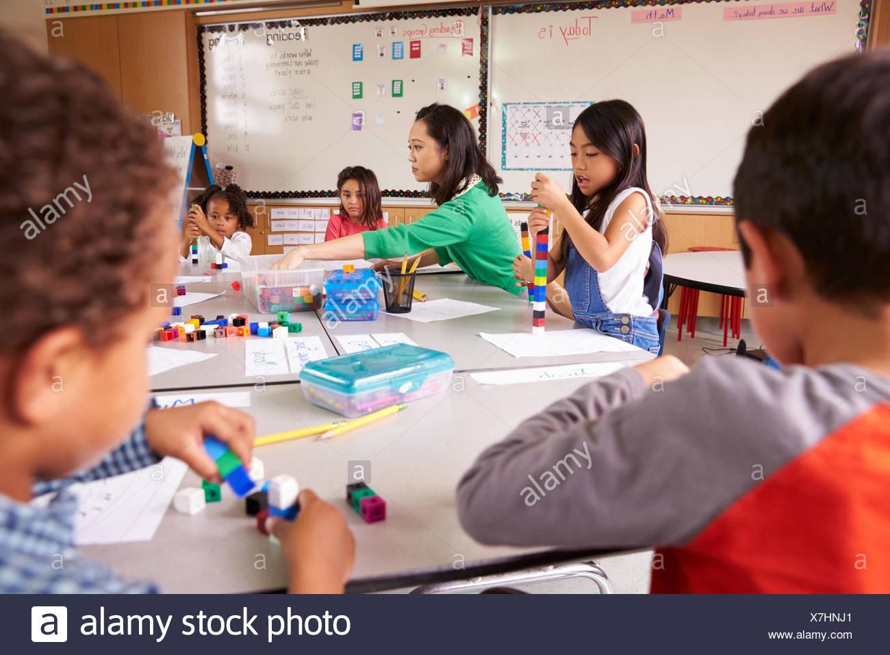 Enseignant de l'école élémentaire utilise des jeux de cubes en classe avec les enfants Photo Stock