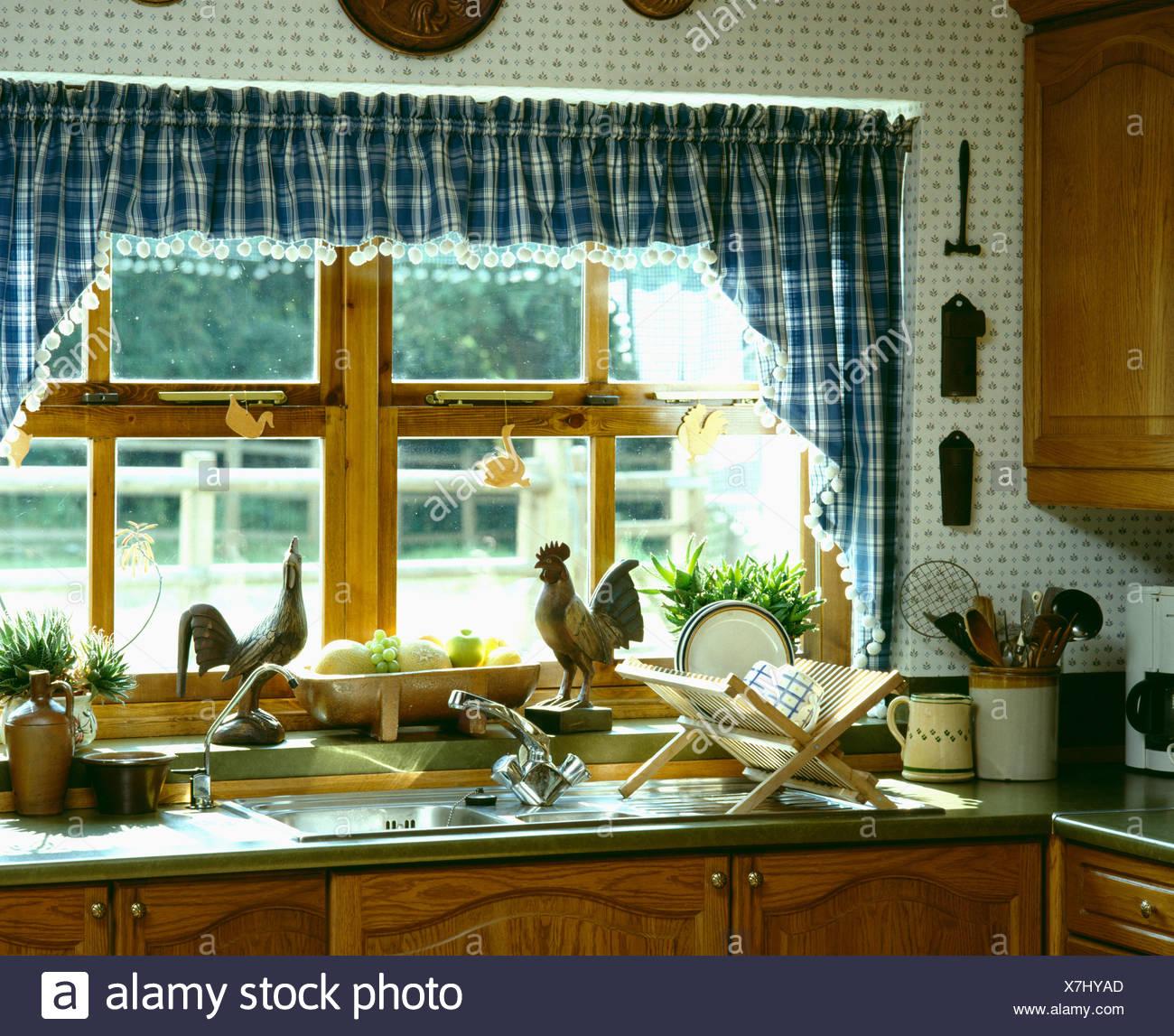 Vichy bleu et blanc vérifié à rideaux fenêtre au-dessus de cuisine ...