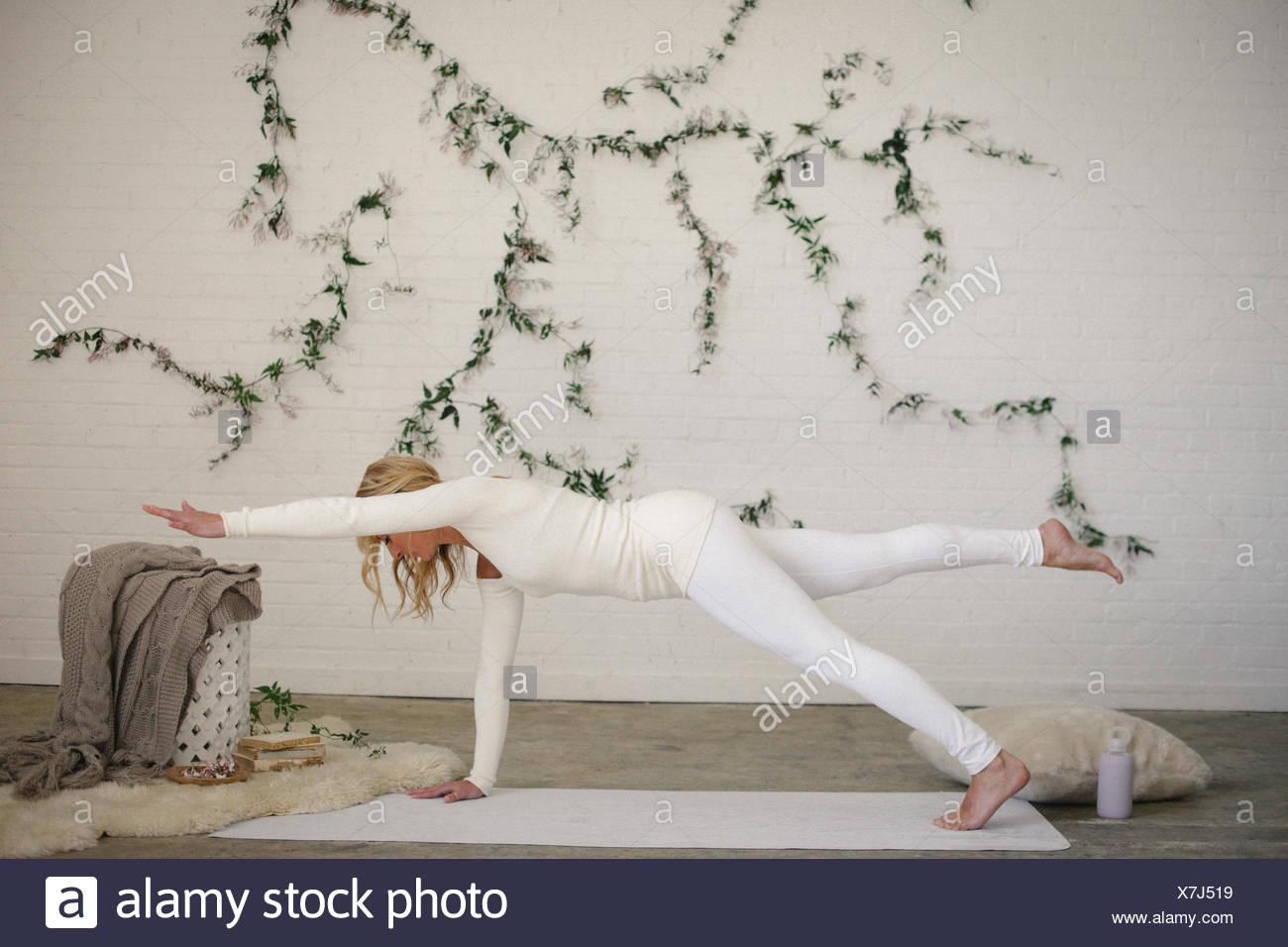Une femme blonde sur un tapis blanc dans une chambre, sa jambe et bras tendus. Une plante rampante sur le mur derrière elle. Photo Stock