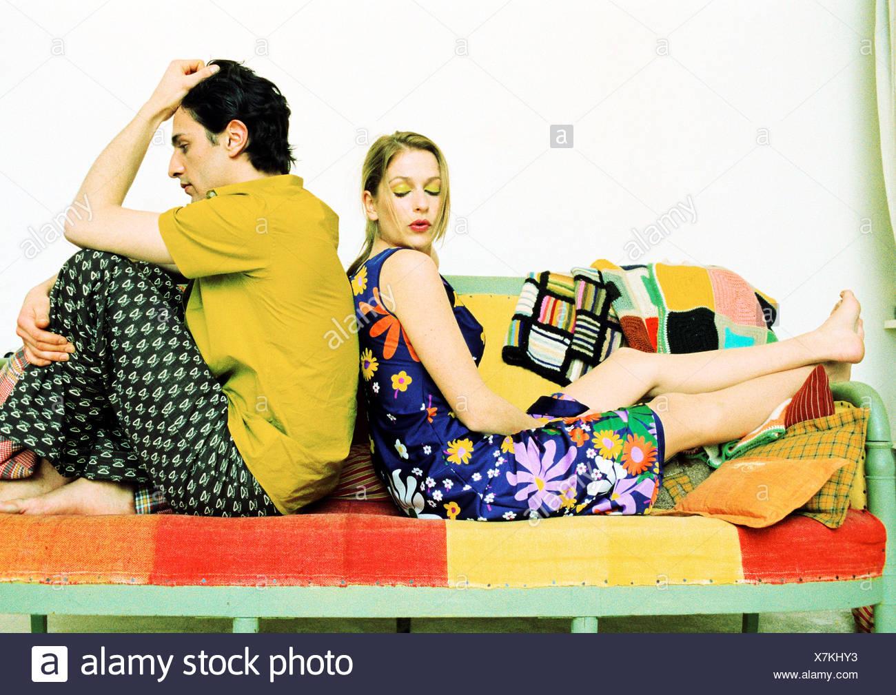 Couple assis sur le canapé, dos à dos. Banque D'Images