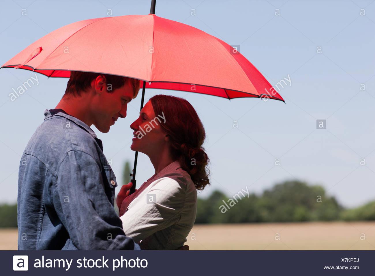Couple hugging sous parapluie rouge Photo Stock