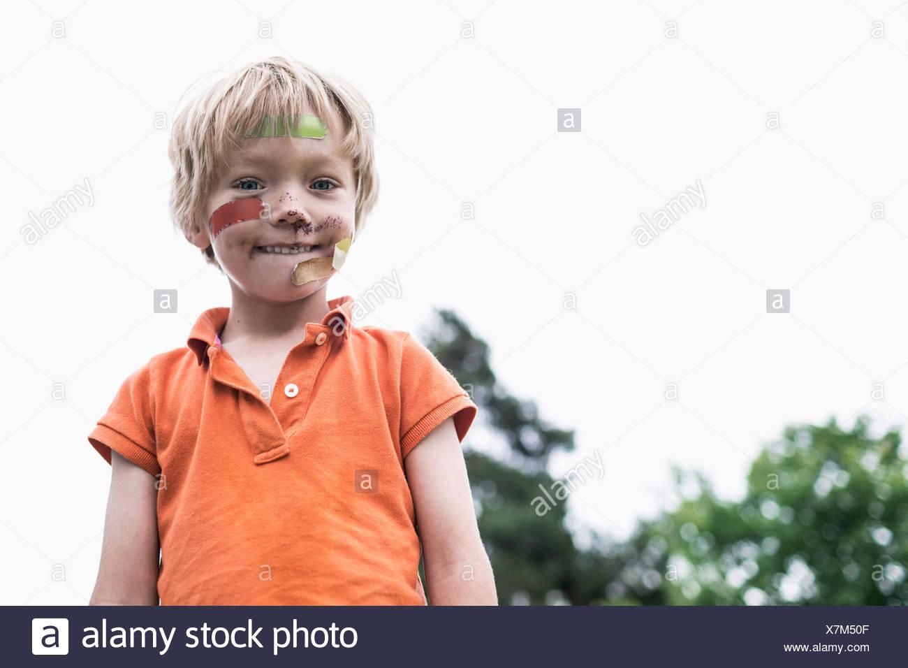 Portrait d'enfant blessé debout contre un ciel clair Photo Stock