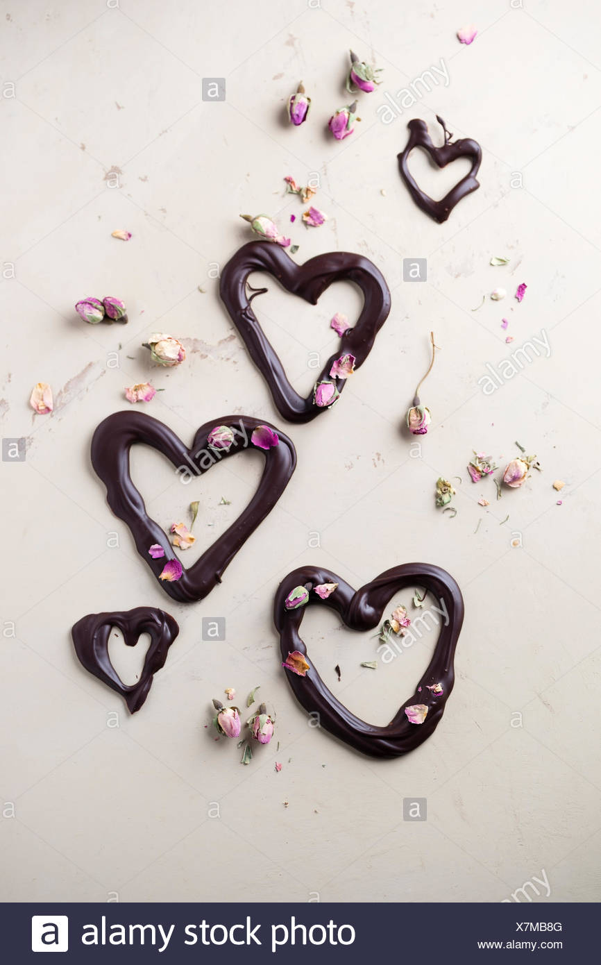 Coeurs en chocolat et rose séchées fleurs sur fond clair Photo Stock