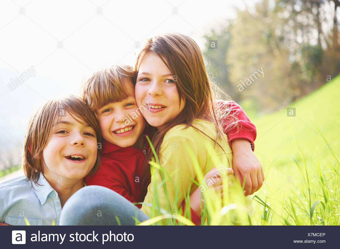 Jeunes Frères et soeur sitting in grassy field Photo Stock