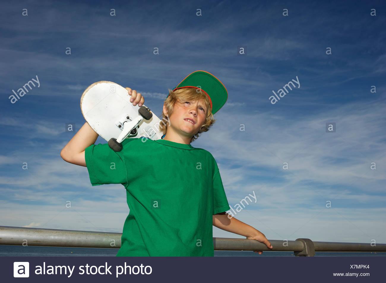 Portrait of boy holding skateboard over shoulder Photo Stock