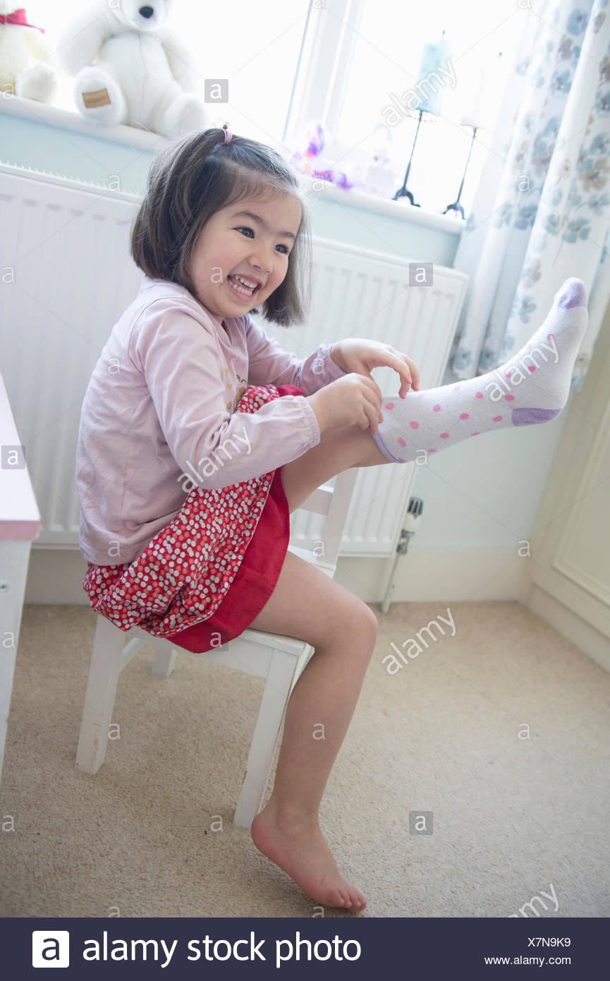 Jeune fille assise sur une chaise, tirant sur chaussette Photo Stock