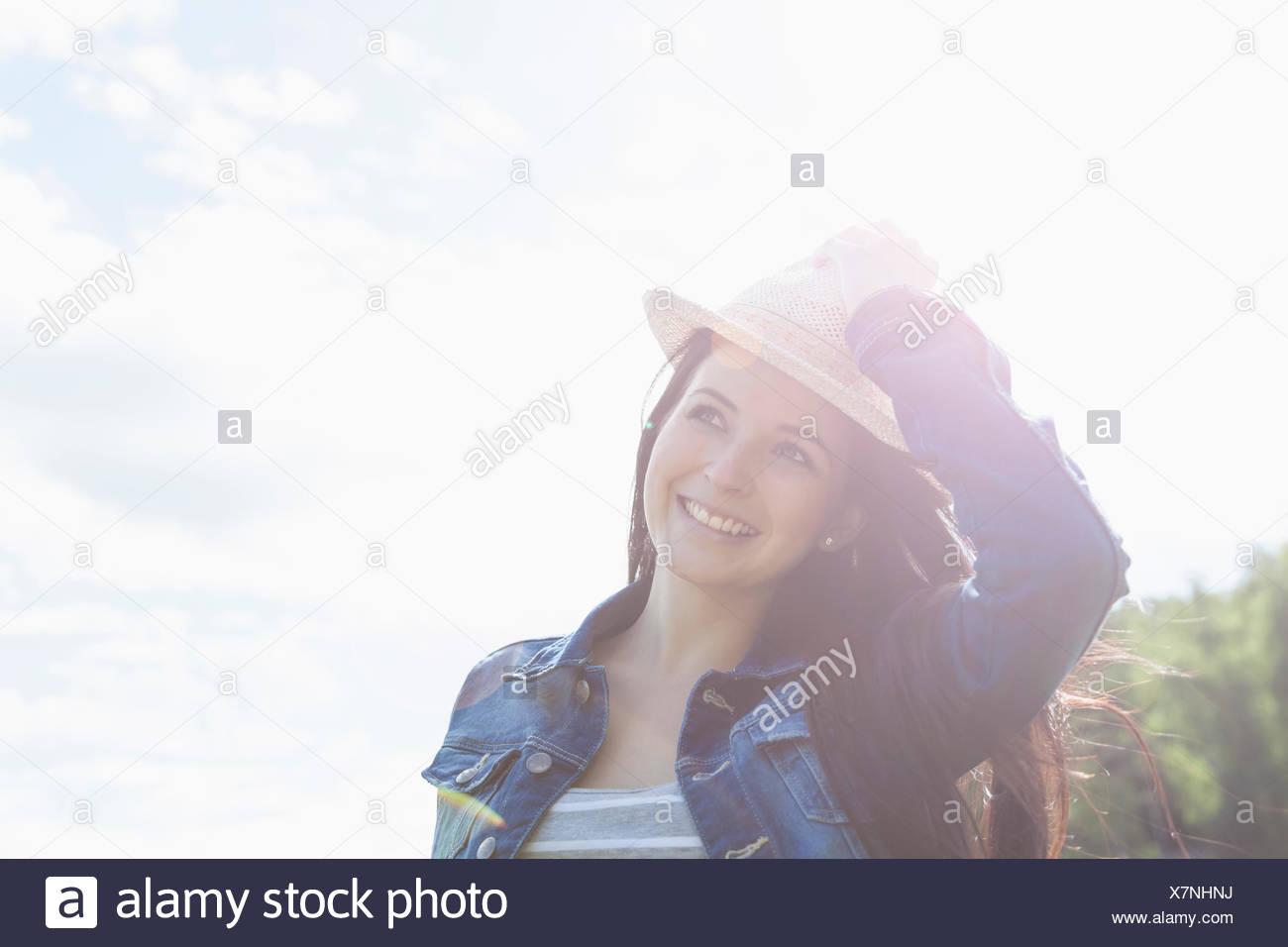 Young woman smiling, la maintenant sur hat Photo Stock