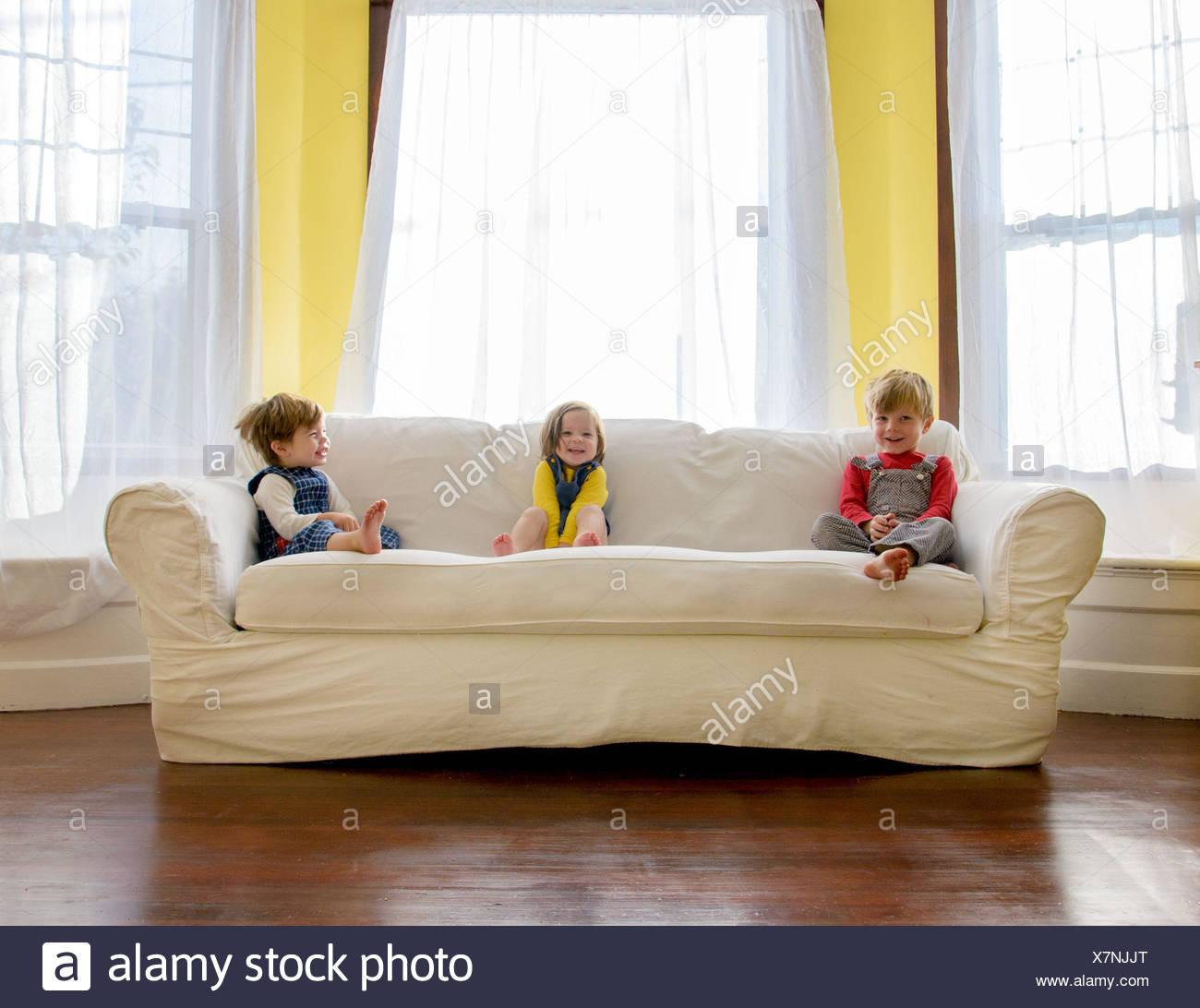 Enfants ( 2-3, 4-5) sitting on sofa Photo Stock