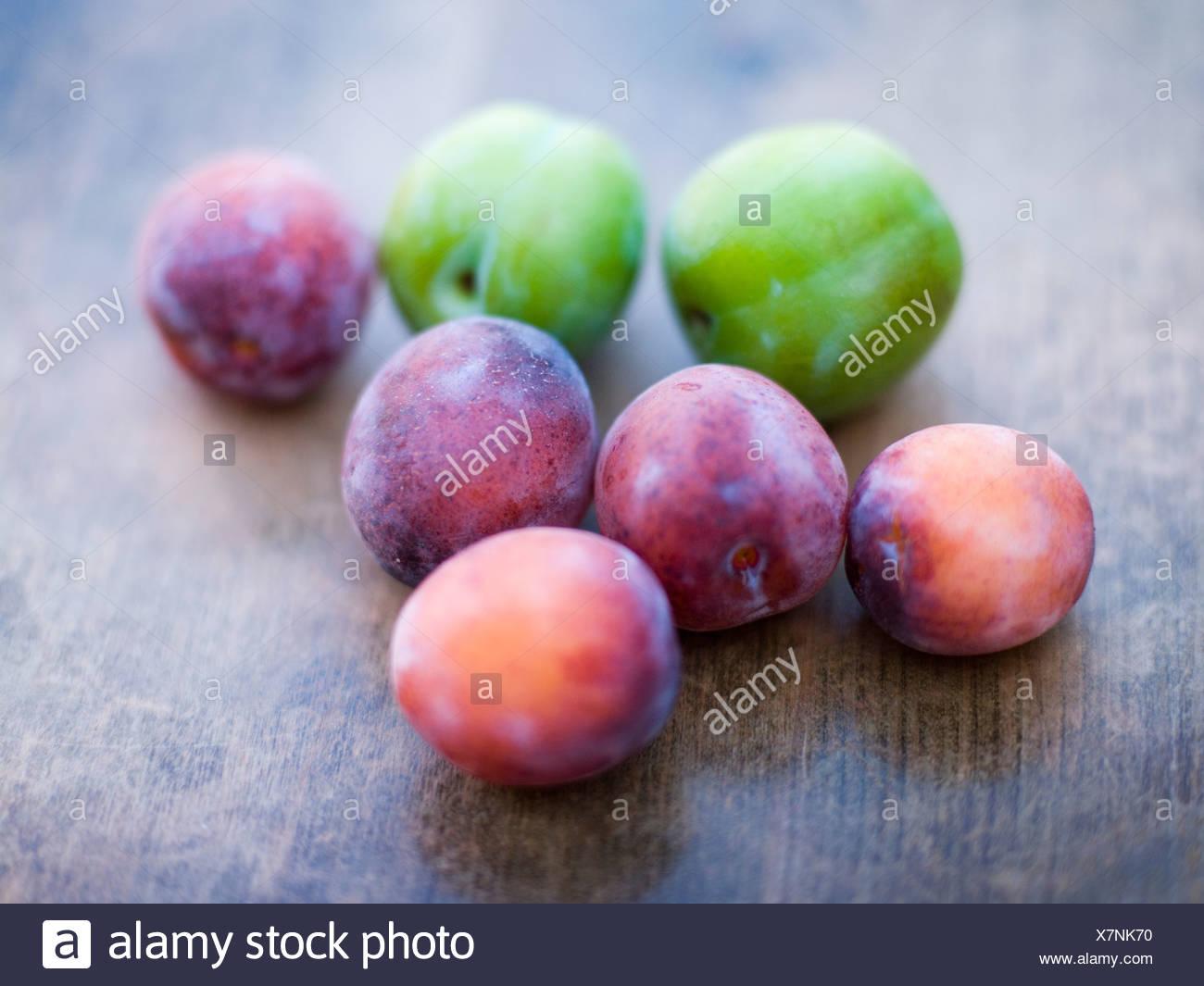 Les prunes vertes et violettes sur table en bois Banque D'Images