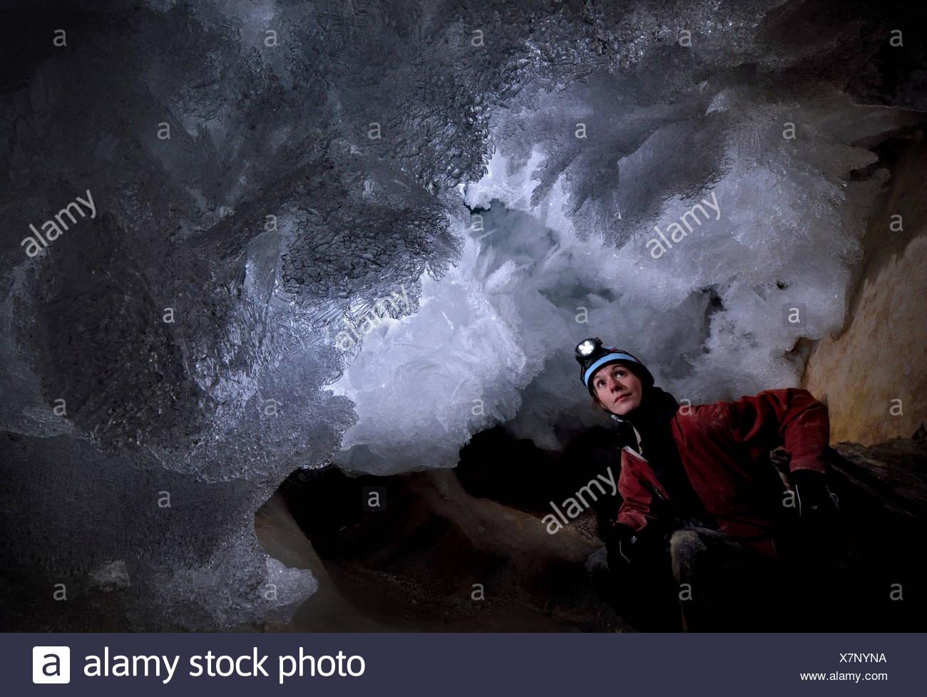 Un scientifique dates la caverne cryogénique de carbonates et examine les délicats cristaux de givre dans le toit d'une petite grotte dans Mammuthoehle Dachstein. Photo Stock