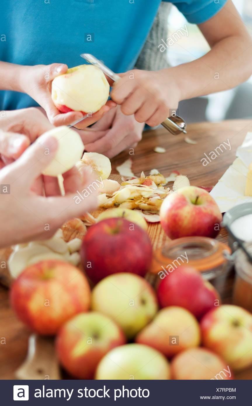 Cropped shot de père et fils mains l'épluchage des pommes biologiques Photo Stock