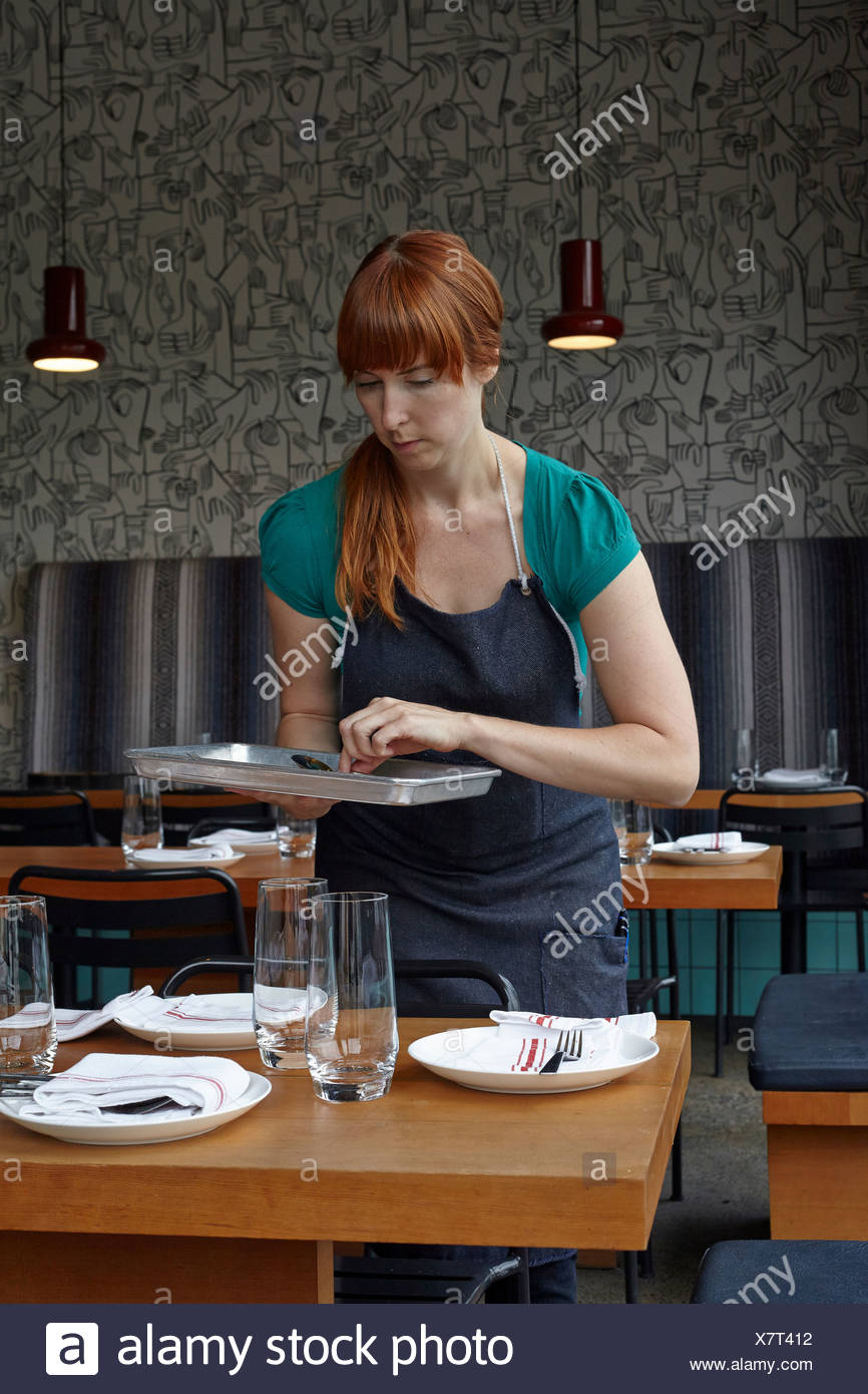 Mid adult woman preparing table in restaurant Photo Stock