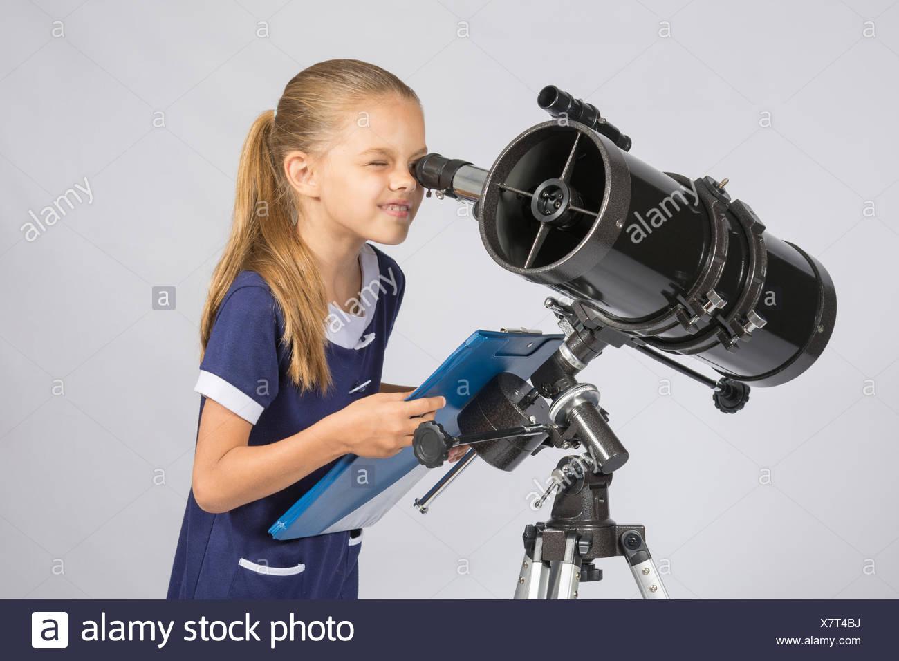 Le jeune astronome heureux de regarder à travers le