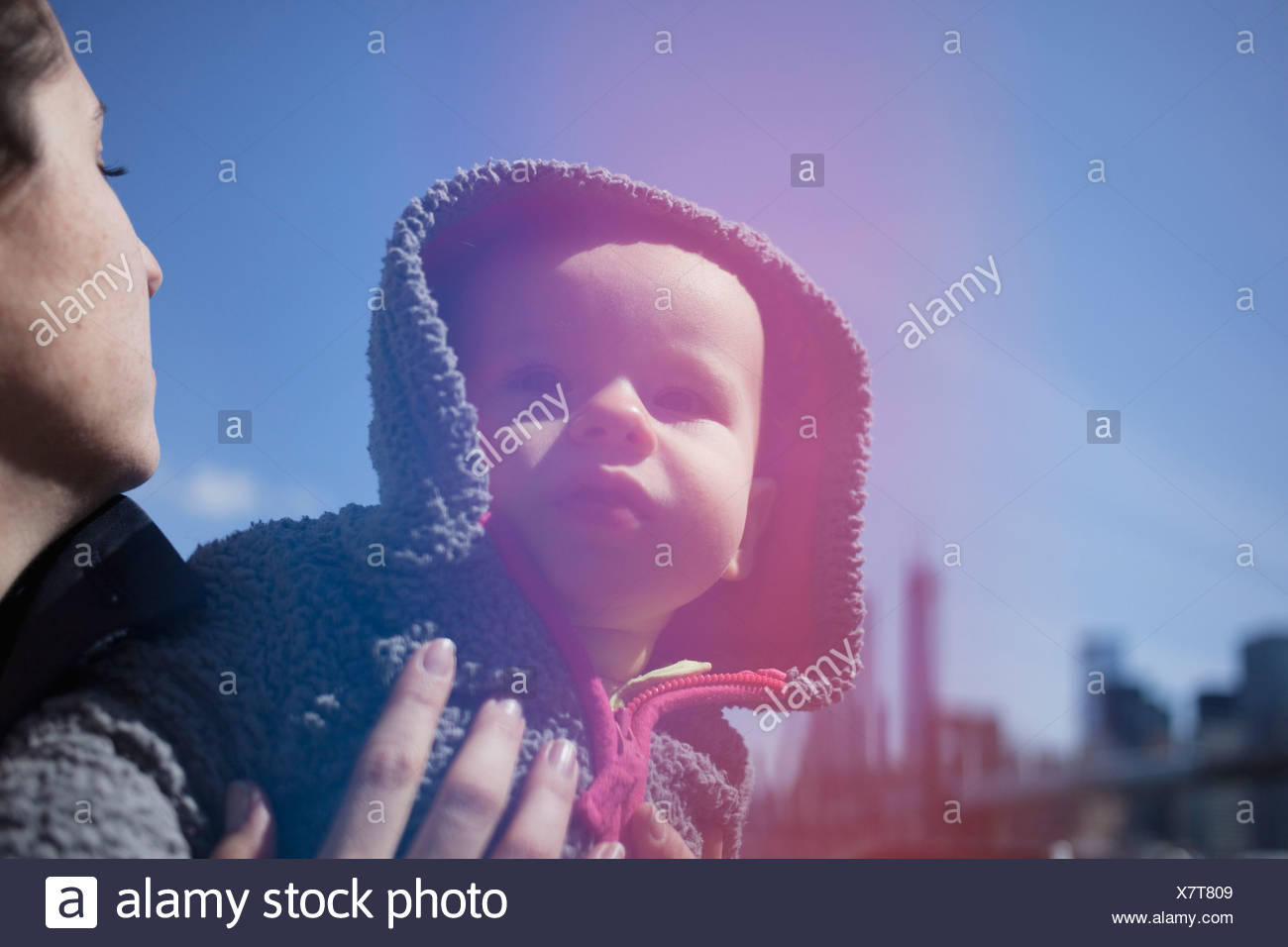 Mother holding daughter wearing hood Photo Stock