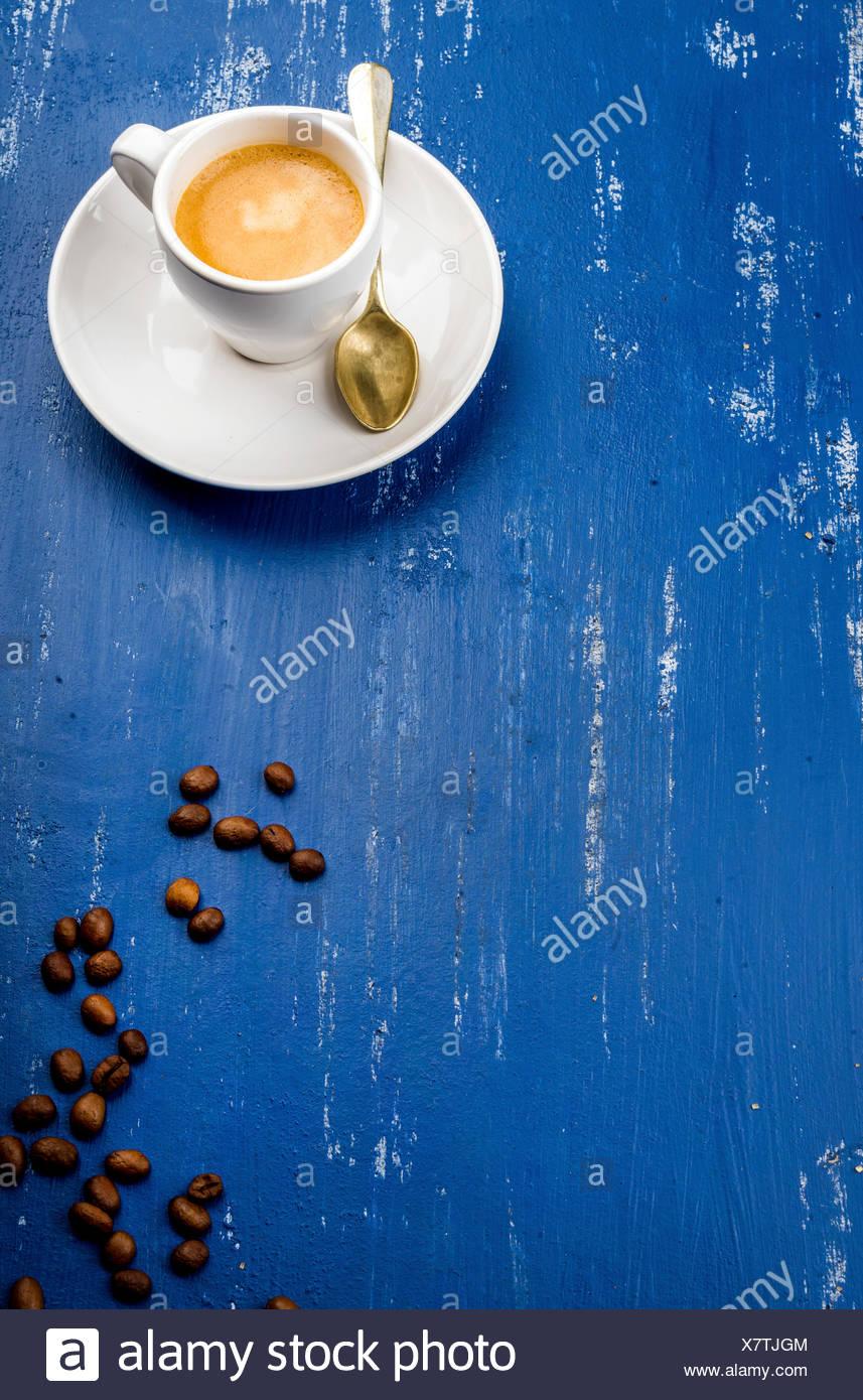 Tasse de café espresso et de haricots sur la table en bois peint bleu arrière-plan. Vue d'en haut, vertical Photo Stock