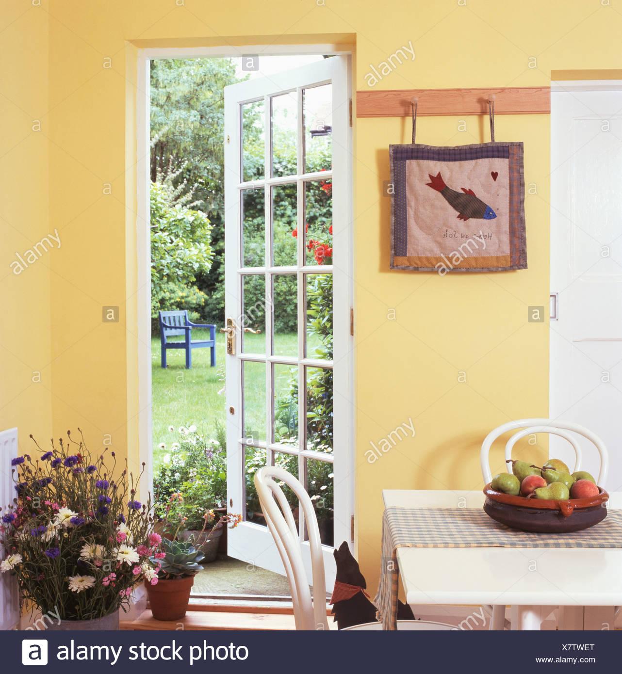Petite cuisine jaune avec porte vitrée ouverte à jardin ...