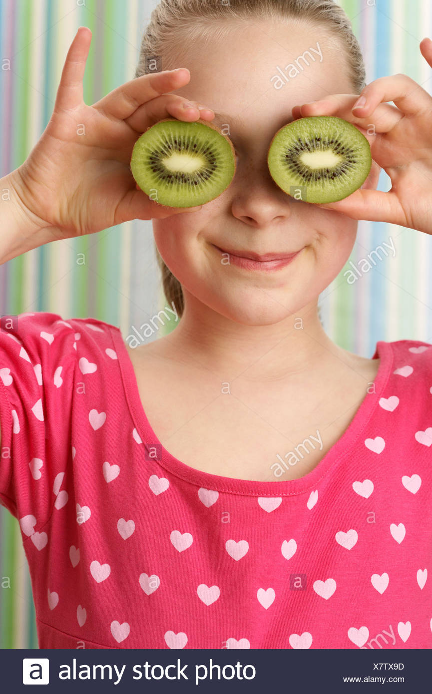 Girl holding kiwis à ses yeux Photo Stock