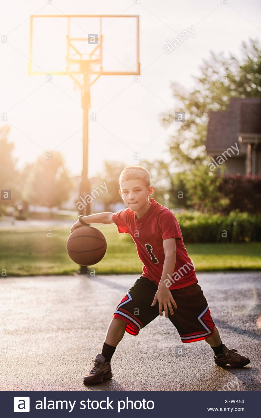 Portrait de jeune garçon dribbler avec le basket-ball Photo Stock