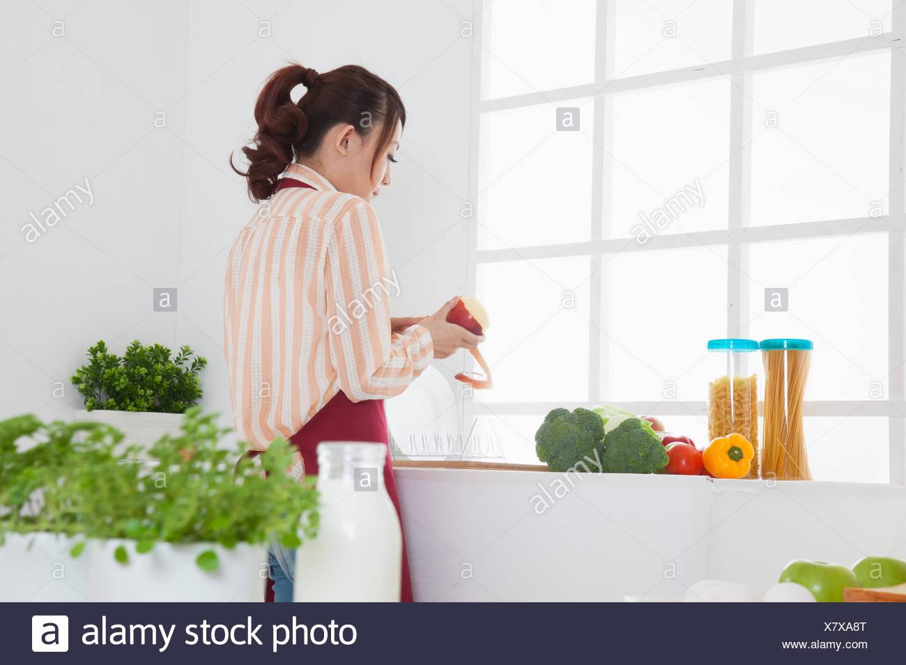 Young woman peeling une pomme dans la cuisine, Photo Stock