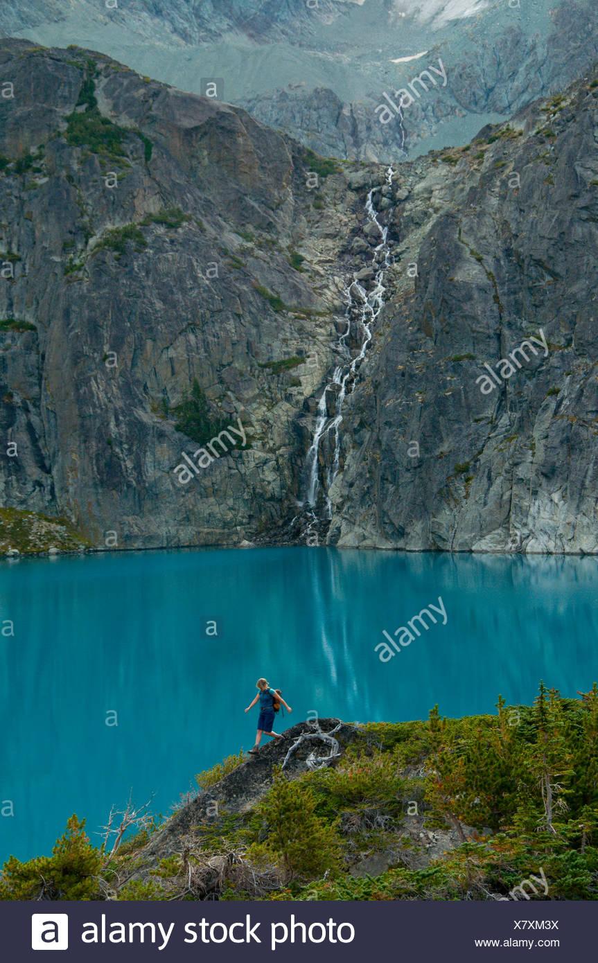 Randonnées d'une jeune femme en face d'un lac bleu et chute d'eau dans la gamme Niut, British Columbia, Canada Banque D'Images