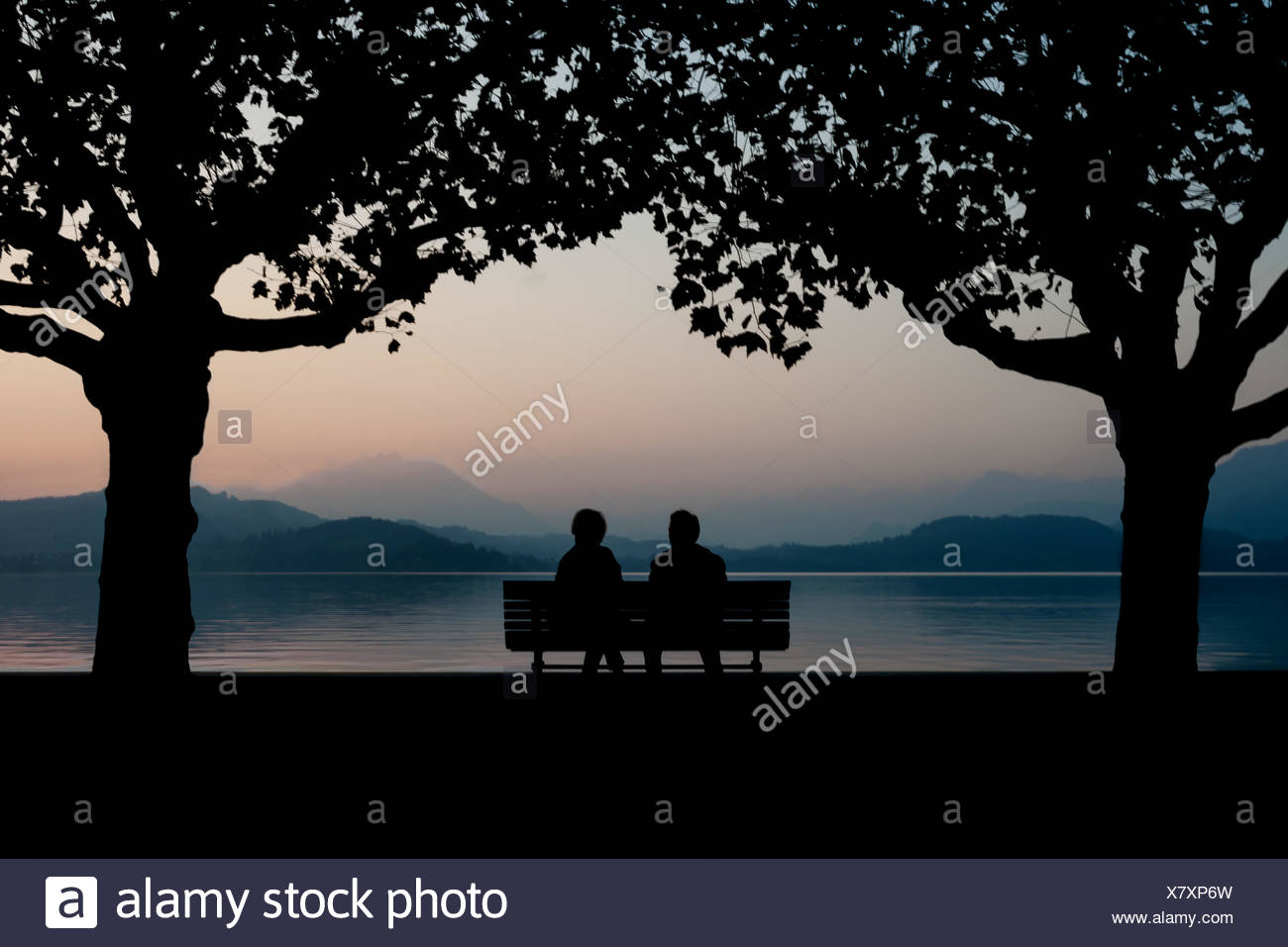 Silhouette Couple Sitting on Bench par Calm lac au crépuscule Photo Stock