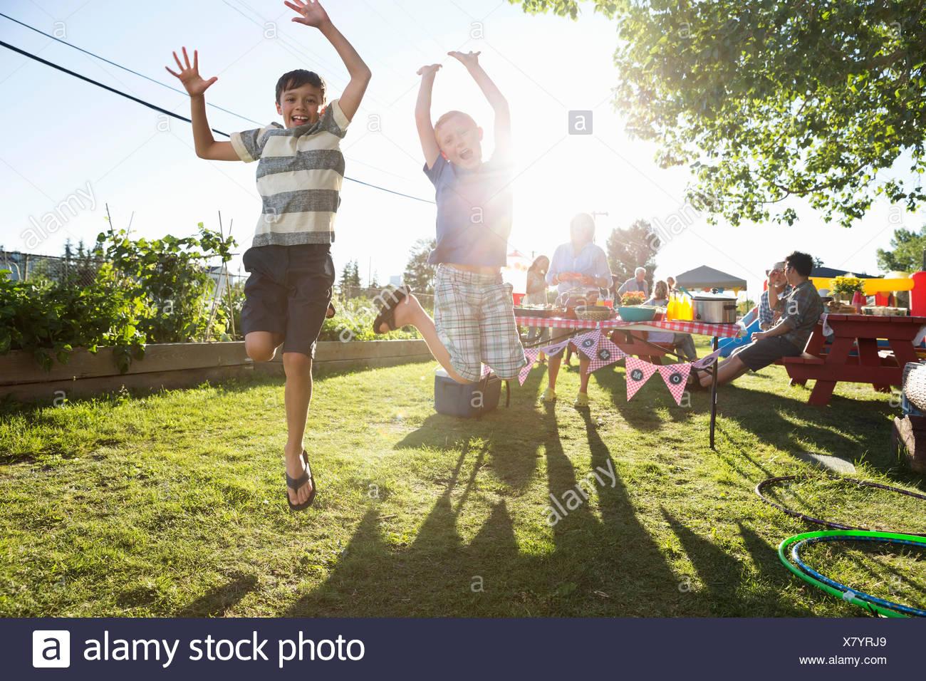 Portrait garçons espiègles sautant de joie sunny park Photo Stock