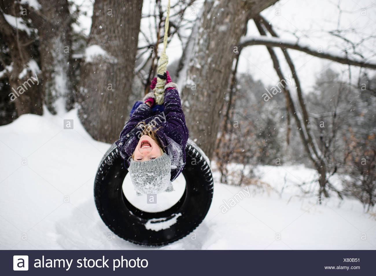 Jeune fille à l'envers sur balançoire pneu dans la neige Photo Stock