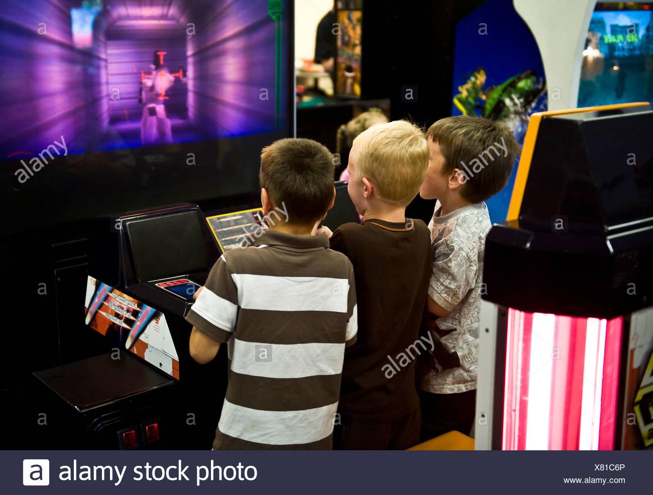 Des garçons jouent à un jeu vidéo dans une arcade Photo Stock