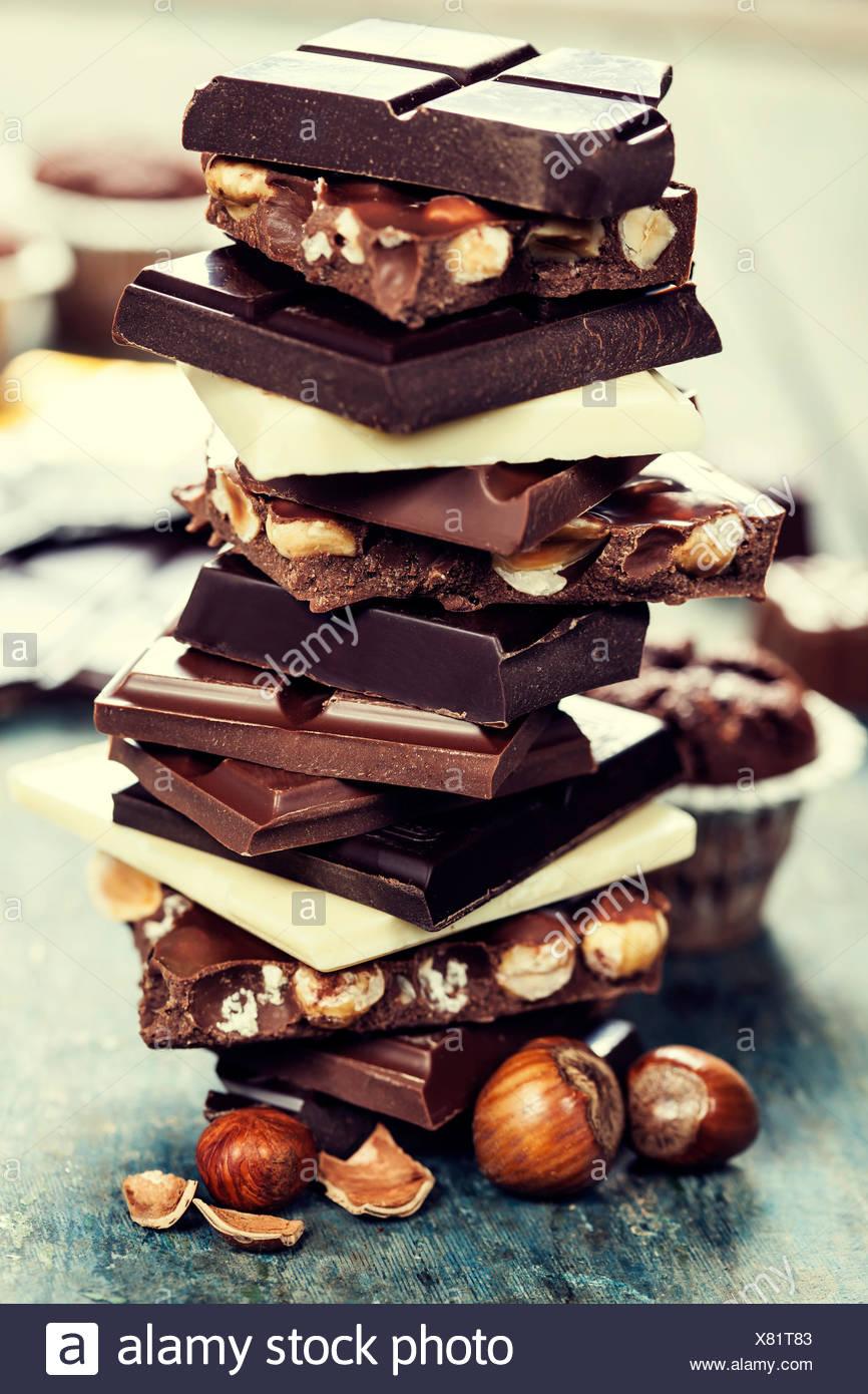 Un assortiment de blanc, noir, chocolat au lait et aux noix - sur planche de bois Photo Stock