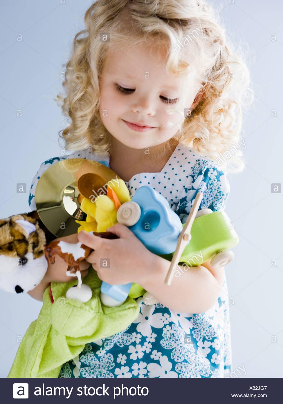 Petite fille tenant une brassée de ses jouets Photo Stock