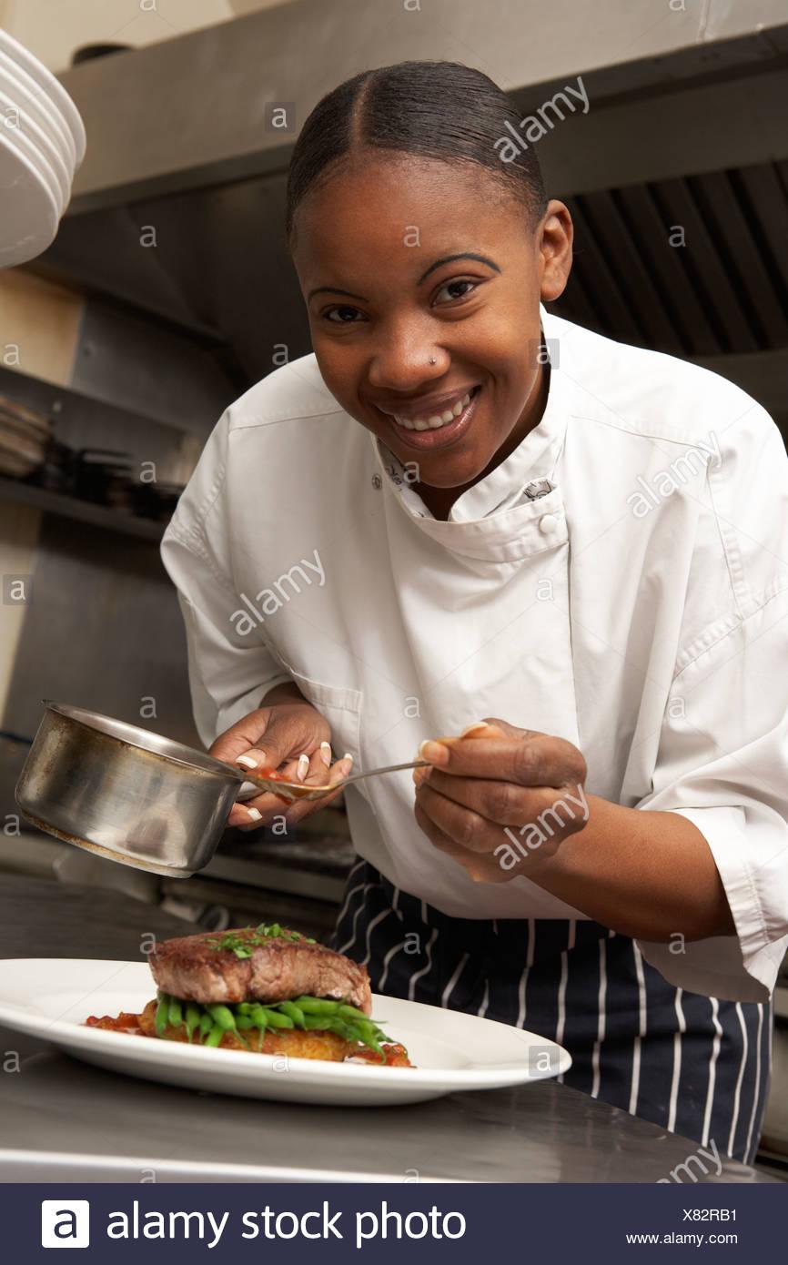 Ajouter à la Sauce Chef plat dans une cuisine de restaurant Photo Stock