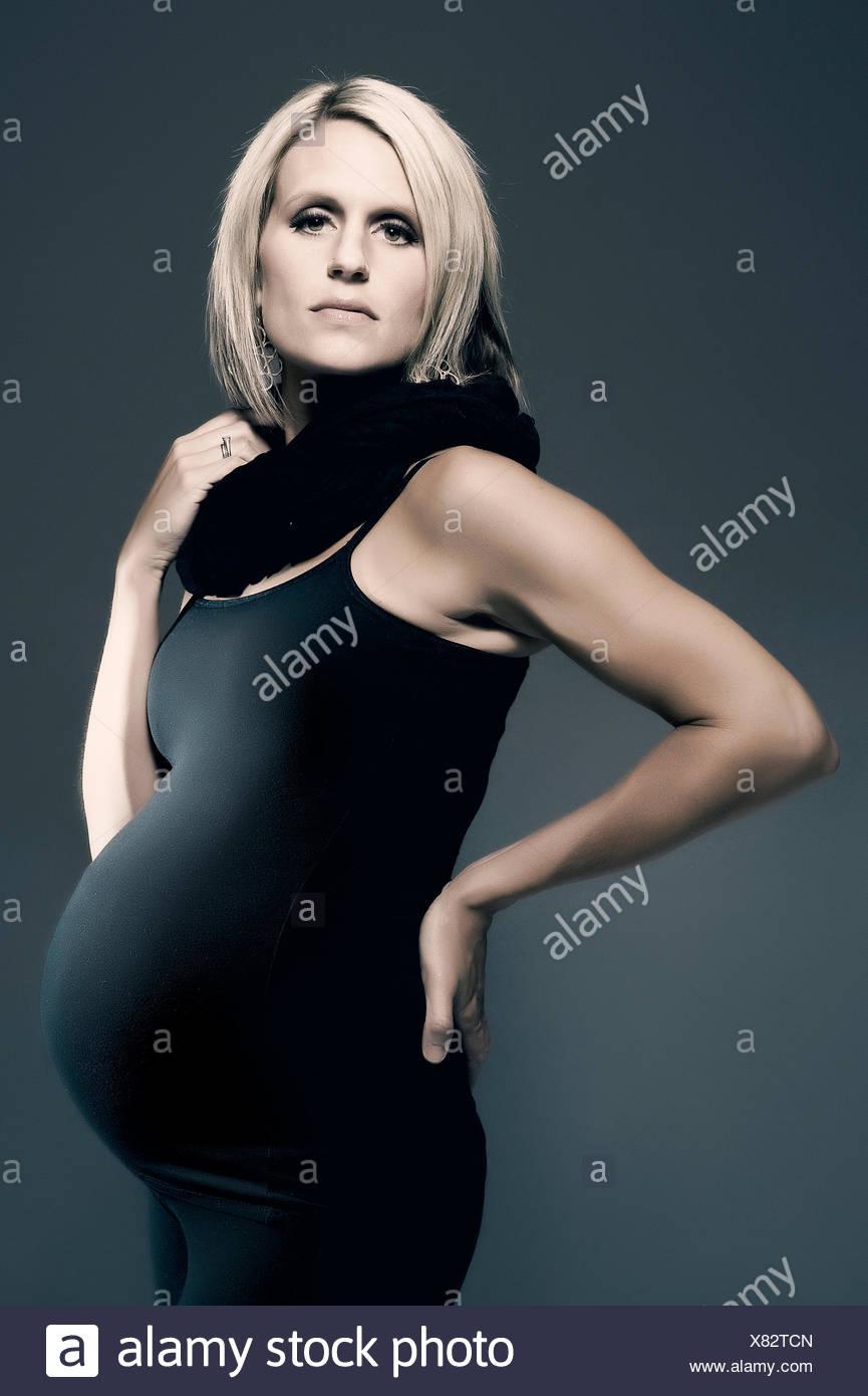 b9e6d907b854 Une blonde femme enceinte se tient dans un profil posent tout en portant un  corps noir serré suite avec un foulard noir.