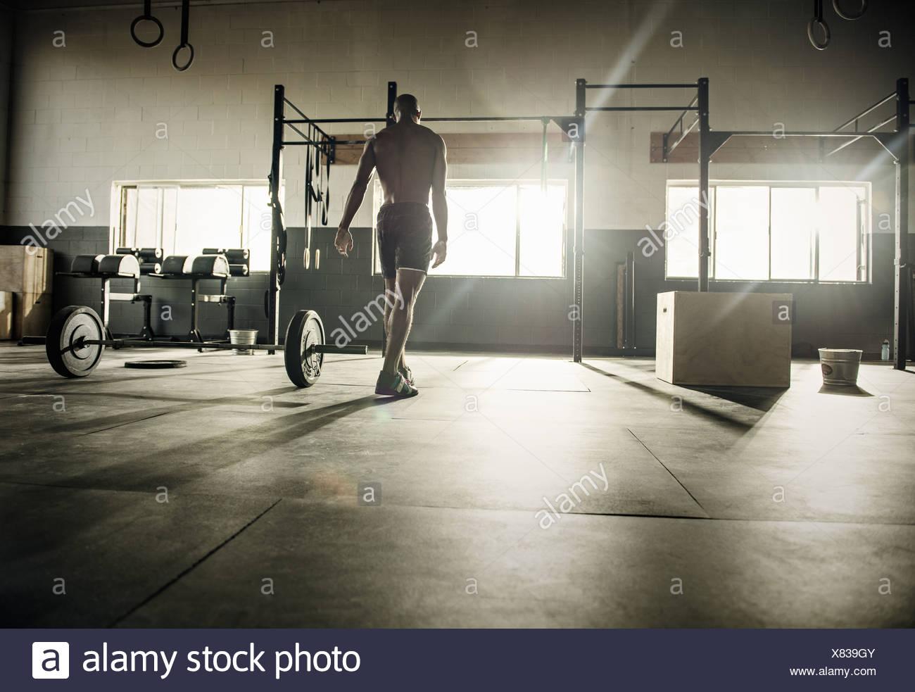 Jeune homme préparait pour l'exercice bar in gymnasium Photo Stock