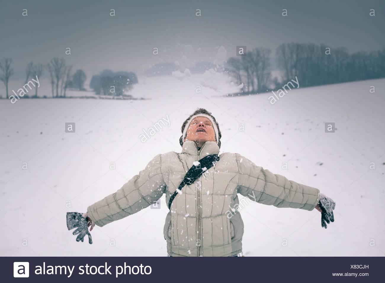Femme d'âge moyen extatique profiter de la neige en hiver. Photo Stock