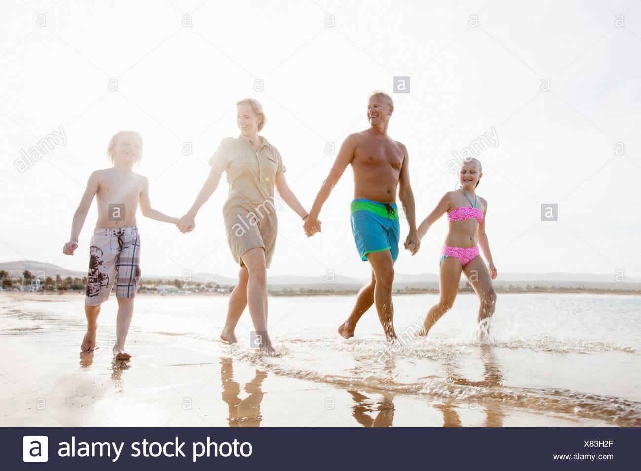 Famille avec deux enfants se promener et on beach Photo Stock
