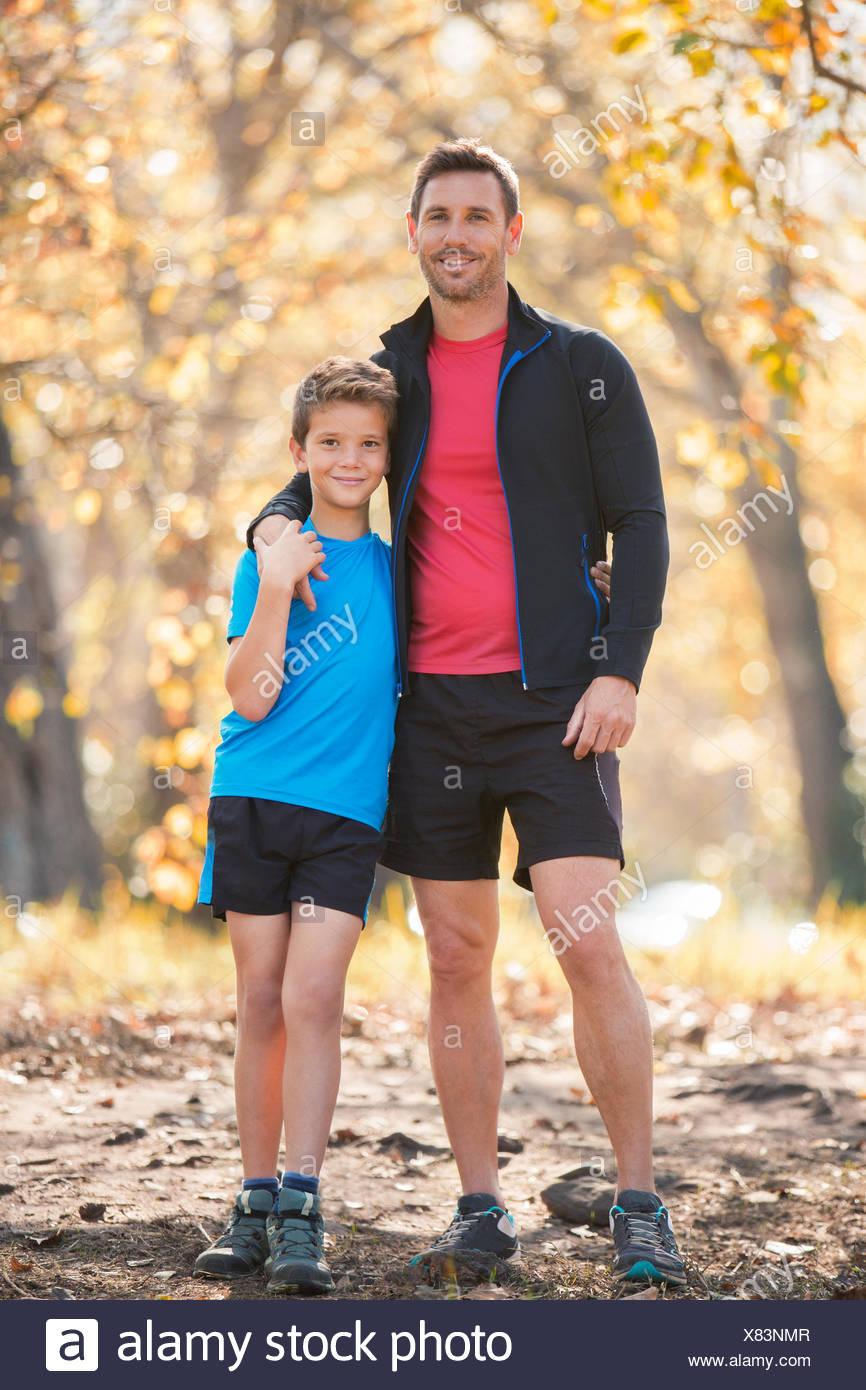 Portrait of smiling father and son in sportswear sur le chemin dans les bois Photo Stock